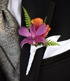 blue orchids,The groom's boutonniere of blue angel orchids, orange celosia and deer fern matched the bride's purple bouquet.