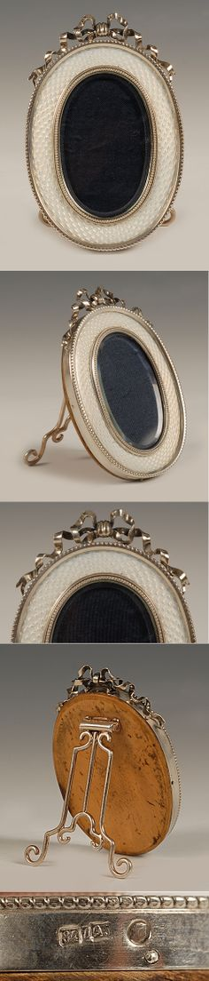 A Faberge silver and guilloche enamel oval frame, workmaster Andrei Gorianov, St Petersburg, circa 1908-1917. Of oval form, the surface decorated in translucent white enamel over a wavy engine-turned ground, the frame surmounted by an undulating silver bowknot; wood back and silver strut.