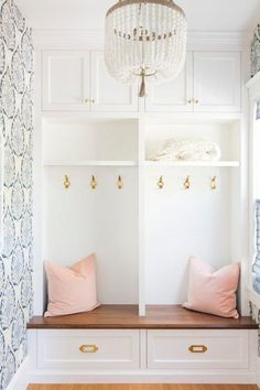 A mudroom with cute pink pillows and super chic wallpaper? I would like to move in right this second, please.