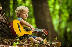 Little boy playing guitar in a forest.