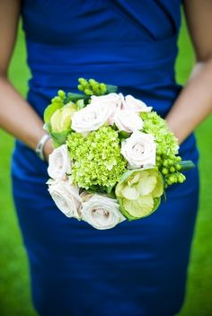 Bright blue bridesmaid's dress with green and white bouquet