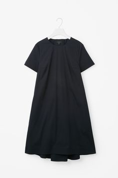 This dress is made from crisp cotton-mix poplin with a grosgrain tie fastening on the back. An A-line fit, it has in-seam pockets, neat short sleeves and a subtly graduated curved hem.