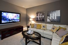 Gray walls and gold and gray pillows on a white L-shaped sofa make an inviting home media room that's also a great room for conversation. From Jimmy Jacobs Custom Homes. Caballo Ranch community. Near Austin, TX.