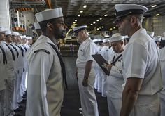 Master Chief Electrician's Mate Nathan Grindeland, right, from Longview, Wash., conducts a uniform inspection aboard the aircraft carrier USS Ronald Reagan (CVN 76).