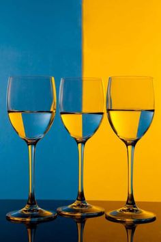 There are three wine glasses. The background is blue and yellow. Each wine glass looks different from the water. Contrast Photography, Glass Photography, Reflection Photography, Still Life Photography, Color Photography, Creative Photography, Digital Photography, Composition Photo, Contrast Art