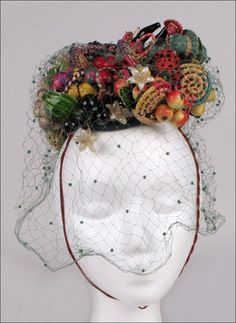 Bes-Ben fruit basket hat entirely covered in raffia baskets containing grapes, lemons, cherries, apples, and flowers. Green veil | Made in Chicago, United States