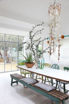 Beautiful Boho dining room with a large table, different pastel colored chairs and a wooden bench. Great mix of plants, natural light and a great pendant light.
