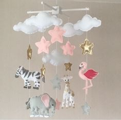 Clouds, stars and jungle animals baby crib mobile. An ideal gift for a new baby's nursery or for room decor in an older child's bedroom.This mobile consists of five white clouds, eleven stars (gold, pale pink and grey) in three sizes and four animals ( giraffe, zebra, elephant and flamingo) The elements are suspended w