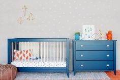 Navy crib and dresser, polka dot wallpaper in child's room
