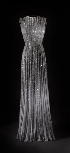 beautiful silver grey columar gown.  Tucks run vertically down the bodice and fall into pleats, gently fan open at the hem. Liberally sparkled with crystals.  A neckline fits along the base of the throat in a boatneck style.  Sleeveless.