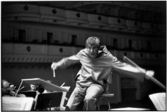 ".New York City. Carnegie Hall.  Photo HCB  Leonard BERNSTEIN, US orchestra director, conducting the New York Philarmonic. In the programm: a piano concert by Franz LISZT and one by TCHAIKOVSKI. Playing the piano : the Soviet Sviatoslas RICHTER.  Rehearsal.  Bernstein is wearing a red leather shirt which Richter is touching.  - ""Isn't it too warm ?"", he asks him  - ""Oh no, it's Dior"", Bernstein answers."