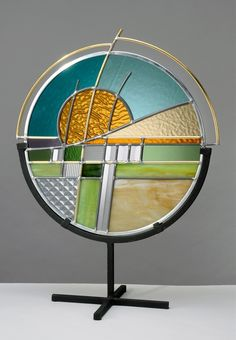 "Round stained glass landscape design made with glass, lead, brass, and zinc with a black steel frame. 12""x6""x18"""