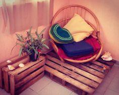 Esquina de casa decorada con una silla vieja de bambú, pallet, caja de fruta o huacal y cojines.