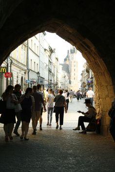 Walking under Brama Florianska, or St. Florian's Gate, onto Florianska Street in Krakow, Poland...