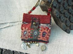 What are you hiding in this little precious pendant bag? It is made with a so beautiful piece of embroidery Banjara hand sewn on the garnet and felt and a small piece of ikat. Always handmade, I hooked it small bronze beads, a small bell, a little star and two small metal Kuchi leaves.. It opens and closes with a piece of leather and a bell. The chain is bronze colored metal with four red beads from a vintage necklace. The bag measures 2,8 inches wide by 3,4 with beads; The chain measur...