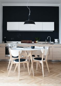 dark wall, light wood kitchen and small chic dining