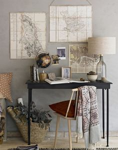 Pale grey walls provide a beautiful background for this interesting use of vintage maps and accessories