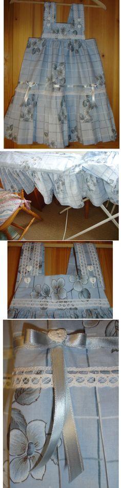 Laget av gardinkappe med rynkekappe. Selekjole med folder og justerbare skulderstropper. Påsydd blonder og bånd. Heter Majakjole for den var laget til et tantebarn som heter Maja.