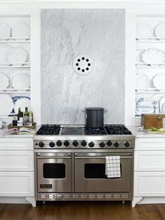 Linda Woodrum's kitchen features a marble backsplash over her professional range that also includes a unique range hood. As seen on HGTV.com.