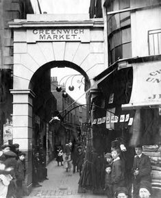 A number of children stand at the entrance to Greenwich Market in Turnpin Lane, Greenwich. The three balls of a pawnbrokers shop are clearly visible under the archway. Early 20th century
