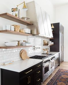 Open shelving, subway tiles, brass hardware and black kitchen cabinets.