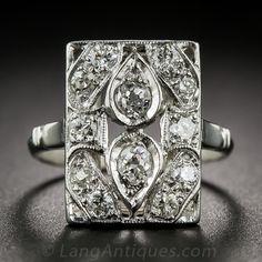 Una placa rectangular, dictada en el platino, centrando un un par de lágrimas de diamante set-back-to-back y tachonada con otros diez diamantes redondos brillantes brillantes blancos lo convierte en un impresionante y sofisticado bengala Jazz-Edad - alrededor del año 1920. 9/16 por 7/16 pulgadas; tamaño del anillo 4 1/2.