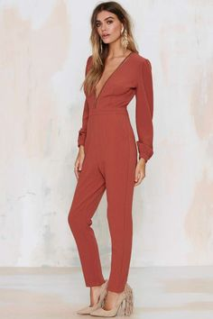 The Take a Dive Jumpsuit comes in rust and features a plunging ladder-trim neckline, elastic cuffs, pleated waist and front pockets.