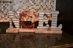 """""""NOEL"""" made from old barn tin (Letters from Junk FX on Etsy), pallet wood, and a berry wreath made from Christmas picks. The letters are glued to wooden dowels to secure them to the base. Love it! Follow me for great DIY home decor projects."""