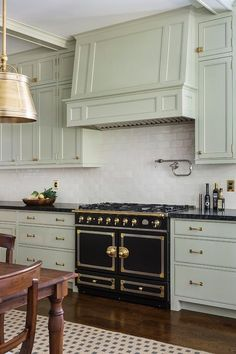 Beautiful kitchen boasts light gray green cabinets paired with black granite countertops and cream glazed tile backsplash.