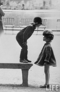 A little boy modeling a two-piece outfit is standing on top of the stoned bench while looking down at the little girl who is wearing a large hat and a coat that is springing to her waist, by Pierre Cardin . Old Pictures, Old Photos, Old Paris, Little Boy Outfits, Boy Models, Black And White Pictures, Black White, French Photographers, Life Magazine