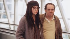 """American Splendor"" movie still, 2003.  L to R: Hope Davis as Joyce Brabner, Paul Giamatti as Harvey Pekar.  Documentarians Shari Springer Berman and Robert Pulcini had just completed their excellent documentary on the life of cartoonist R. Crumb and turned their attention on cartoonist Harvey Pekar.  Half dramatized, half documentary, this film already had a built-in cult following thanks to the work of Pekar."