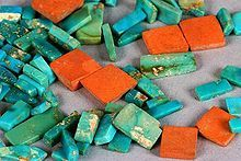 A selection of Ancestral Puebloan (Anasazi) turquoise and orange argillite inlay pieces from Chaco Canyon (dated ca. 1020–1140 CE) show the typical colour range and mottling of American turquoise.