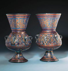 "A PAIR OF LARGE MAMLUK STYLE ENAMELLED GLASS MOSQUE LAMPS  Each of typical form with rounded body on spreading trumpet foot rising to a flaring conical mouth, six simple loop handles around the body, body with panels of brightly coloured floral designs between blue floral meander stripes, a band of similar brightly coloured floral designs below, mouth with a band of gold thuluth titulature on a scrolling gold and blue ground, minor floral band above, the foot with similar floral designs, 20""…"