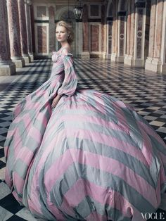 Kirsten Dunst photographed at the peristyle of the Grand Trianon at the Château de Versailles in a corseted pink-and-dove taffeta-and-chiffon ball gown by Alexander McQueen.