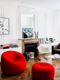 Poltrona e Puff vermelhos em living com lareira clássica