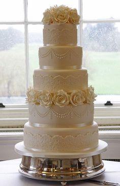 Torta de boda de color blanco con cinco niveles, un estilo vintage con encaje, perlas y rosas. #TortaDeBoda