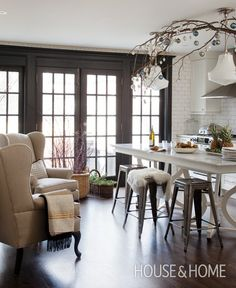 Open-Concept Kitchen; white table-like modern island; black trimmed french doors; dark hardwood floors; white subway backsplash tile to the ceiling; white milk glass pendants
