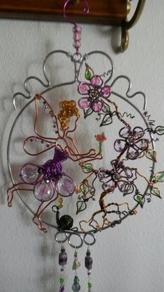Wire wrapped beaded sun catcher with flowers and ladybugs and garden fairy.
