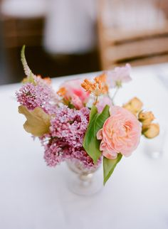 Cheerful centerpieces featuring lilacs, roses, and veronica arranged in silver compotes.  Photo by Rebecca Yale Portraits  Venue: 501 Union  Planner: Jove Meyer Events  Flowers: August Sage and Violet