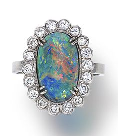 An opal and diamond ring centering an oval-shaped cabochon opal, surrounded by round brilliant-cut diamonds in a plain mount; opal weighing approximately: 6.00 carats; mounted in platinum