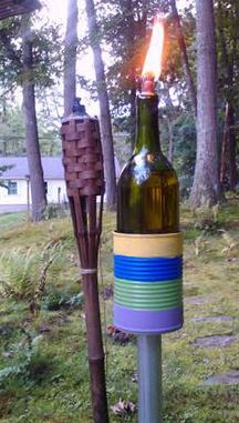 Out with the old, flimsy tiki torches! In with permanent torches made from some wine bottles.  Galvanized pipe is concreted into the ground, Progresso Soup cans are painted, and bottle is in place. I put small river rock from craft store in bottom of bottle to save on fuel needed.