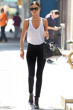 Queen of Street Style Miranda Kerr in high-waisted jeans with a white tank and Saint Laurent boots.