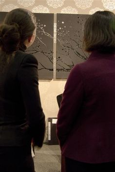 My daughter (l) and a visitor are looking at en talking about the paintings my daughter had made.