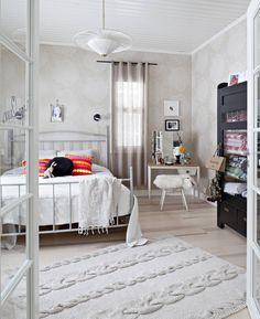 Olohuoneen kupeessa lasiovien takana oleva makuuhuone on aikamatka menneisyyteen, muttei mihin tahansa vuoteen vaan sinne tänne. Kitsch-ikonit, 1940-luvun kattovalaisin, 1970-luvun kampauspöytä, neulematto ja pikimustan maalin pintaansa saanut talonpoikaisantiikkinen liinavaatekaappi luovat harmonisen kokonaisuuden. Matto on HK Livingin mallistosta ja vuode Iskusta.