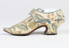 Pair of lady's shoes, ca. 1720-1730. White kid embroidered in imitation of brocade with large carnations and other blooms, edged in pale blue silk ribbon, straights, with narrow white rand, sharply pointed overhang toe-tip, low curved, heel, lined in linen.