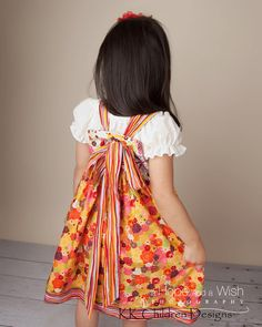 could make this--just make button holes on the back and thread the sash through. Love the big bow in the back!