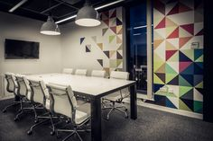 Quidco Office, meeting room with custom steel frame table with corian top, reclaimed industrial lights and custom wall graphics. Interior Design  |  www.jimbutterell.com