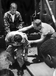 Back at Da Nang, wounded Sergeant Owens is eased out of the copter by Farley and a fellow Marine. (Photo by Larry Burrows/Time & Life Pictures)