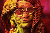 An old man covered in yellow and red color during the festival of colors, Holi, India. by Poras Chaudhary