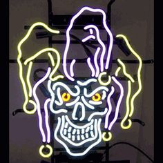 "JESTER SKULL NEON SIGN-NN5JESTR  20"" wide, 23""high, 4"" deep  For those with a darker sense of humor, try our Jester Skull Neon Sign, featuring multi-colored, hand blown tubing supported on a black, finished metal grid. The Jester Skull Neon Sign can be displayed flat on a wall or in a window or alternately be placed upon a shelf."
